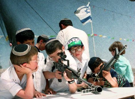 Young Israeli settlers play with army guns 14 Apri