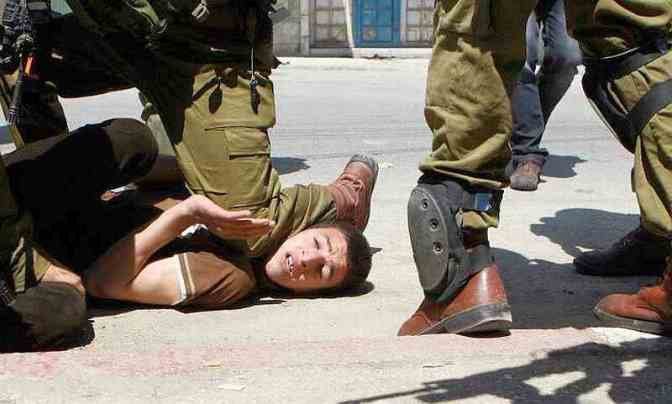 Brave Jewish soldier knee on the neck of unarmed Palestinian boy. Musaid Qawasma