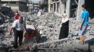 Gaza - 26 July pulling more from rubble family looks on