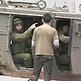 Jewish soldier ordering boy to stand in front of vehicle as human shield