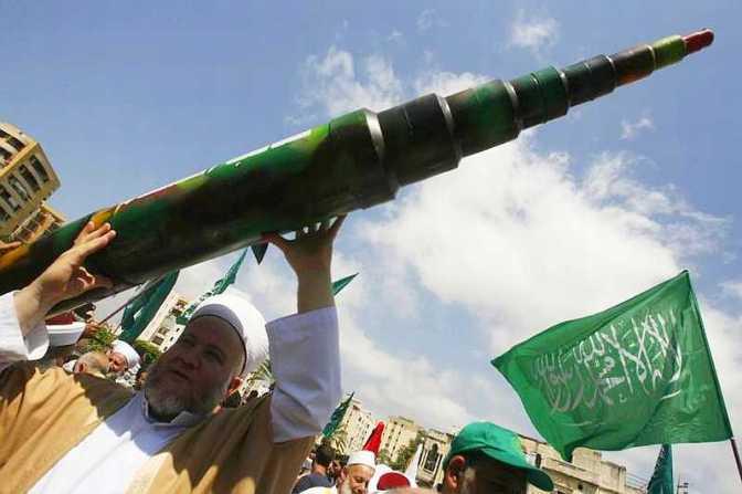 Man holds mock Qassam rocket. AFP/Mahmoud Zayyat