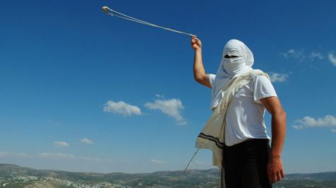Masked violent Jewish settler colonist with slingshot