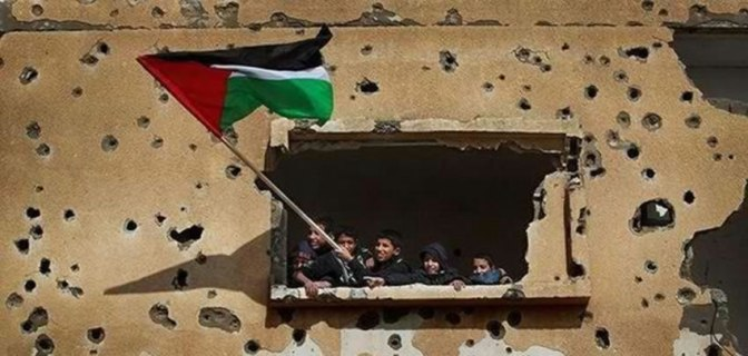 Palestinians wave flag from inside building bombed by Jews