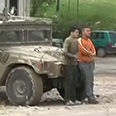 Two boys standing in front of military vehicle as human shields