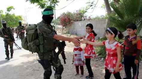 al-Qassam fighter shaking little girl's hand. Wael Abo Omar