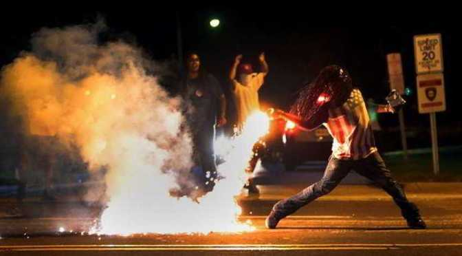 Black man wearing us flag shirt throwing tear gas cannister back at police in Ferguson MO USA